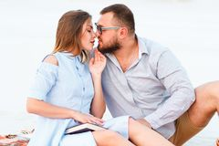 Lovely attractive couple sitting together on the white sand beach, looking each other, young couple kissing on the beach, love, stock photo