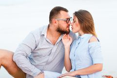 Lovely attractive couple sitting together on the white sand beach, looking each other, young couple kissing on the beach, love, royalty free stock photography
