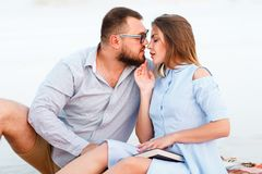 Lovely attractive couple sitting together on the white sand beach, young couple kissing on the beach Stock Photo