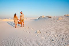 Lovely attractive couple on the white sand beach or in the desert or in the sand dunes, guy and a girl with a basket in their hand. S, the couple left traces or Royalty Free Stock Image