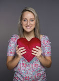Lovely attractive girl with heart in hands. Over grey background Stock Photos