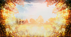 Lovely autumn nature background with trees foliage , sky, field and sun rays. stock image