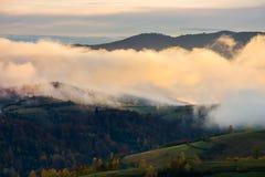 Lovely autumn scenery of mountainous rural area. Cloud inversion at dawn. lovely autumn scenery of mountainous rural area stock photo