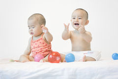 Lovely babies. A pair of Chinese babies are sitting in bed and playing very happily Royalty Free Stock Photo