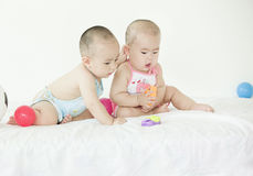 Lovely babies. A pair of Chinese twinborn babies are playing with toys in bed Stock Images