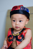 Lovely baby. Crawling Clever Oriental baby on the bed and Wearing a costume, curious expression on his face Royalty Free Stock Photography