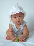Lovely baby. A cute baby with a hat is playing on a bed royalty free stock photography