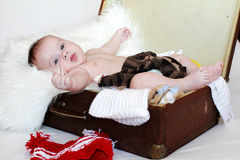 Lovely baby age of 3 months lies in a suitcase with clothes Stock Images