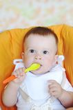 Lovely baby age of 9 months with spoon. On baby chair Stock Image
