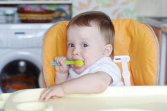 Lovely baby age of 11 months with spoon. On kitchen Royalty Free Stock Images