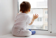 Lovely baby age of 1 year looks out of window in winter Royalty Free Stock Image