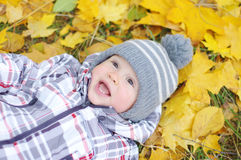 Lovely baby age of 1 year lying against yellow leaves Royalty Free Stock Photos
