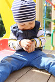Lovely baby with beetle on playground Royalty Free Stock Image