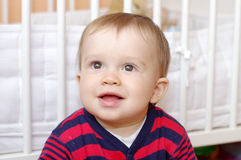 Lovely baby boy age of 1 year against white bed Royalty Free Stock Photo