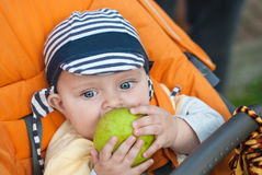 Lovely baby boy outdoor eating apple Royalty Free Stock Photo