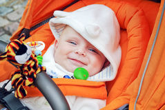 Lovely baby boy outdoor in orange stroller Stock Images