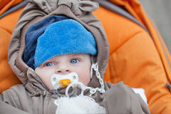 Lovely baby boy outdoor in orange stroller Stock Images