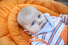 Lovely baby boy outdoor in orange stroller Stock Photos
