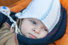 Lovely baby boy outdoor in orange stroller Stock Photo
