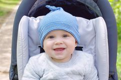 Lovely baby boy outdoors on baby carriage. Lovely baby boy age of 8 months outdoors on baby carriage Royalty Free Stock Photography
