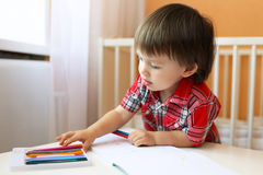Lovely baby boy painting with wax pencils Royalty Free Stock Photos