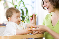 Lovely baby boy playing with food while eating. Stock Photos
