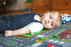 Lovely baby boy playing at home. Adorable cute boy on ground, playing with different toys. Baby with blue eyes looking at the camera Royalty Free Stock Images
