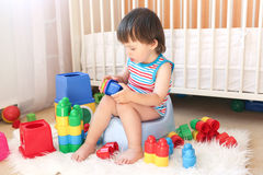 Lovely baby boy plays toys sitting on potty Royalty Free Stock Photo