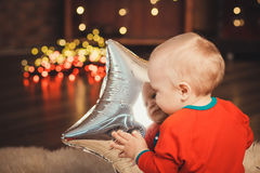Lovely Baby boy in Santa Claus costume for Christmas playing wit Royalty Free Stock Images