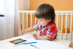 Lovely baby boy with wax pencils at home Royalty Free Stock Photography