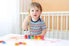 Lovely baby with brush and paints Stock Photos
