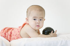 A lovely baby. A Chinese baby is interested in playing pumpkin in bed Royalty Free Stock Photo