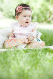 A lovely baby. A Chinese baby is sitting on grass and smiling outdoor Stock Photos