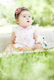 A lovely baby. A Chinese baby is very lovely on grass with tape flower hat on head Royalty Free Stock Photo
