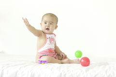 A lovely baby. A Cninese baby is sitting and raising hand in bed happily Stock Images