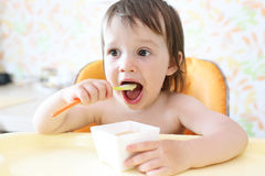 Lovely baby eating fruity puree by himself Stock Image