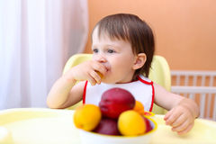 Lovely baby eating peaches and apricotes Stock Photo