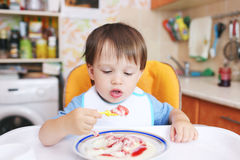 Lovely baby eating semolina porridge Stock Images
