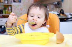 Lovely baby eating soup Stock Images