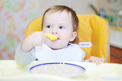 Lovely baby eats cereal. Lovely baby age of 1 year eats cereal Stock Images
