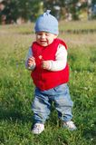 Lovely baby with flowers outdoors. Lovely baby age of 11 months with flowers outdoors Royalty Free Stock Photography