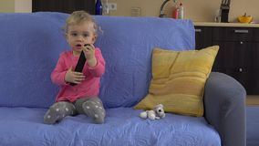 Lovely baby get tv remote control and concentrate on watching television. Lovely baby girl get tv remote control and concentrate on watching television. Static stock video