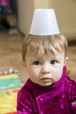 Lovely baby girl with glass on head. Portrait of funny little one year old baby girl with plastic glass on head Royalty Free Stock Photos
