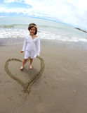 Lovely baby girl inside a heart on the beach Royalty Free Stock Images