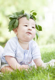 A lovely baby on grass. A Chinese baby is sitting on grass with a branch hat on head Royalty Free Stock Image