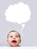Lovely baby looking up, thinking and dreaming stock photo