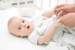 Lovely baby lying in cradle and holding mother`s hands. Insomnia and sleep disorders concept Royalty Free Stock Photography