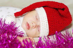 Lovely baby in New Year's hat sleeps among spangle Stock Photo