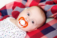 Lovely baby with pacifier Stock Images
