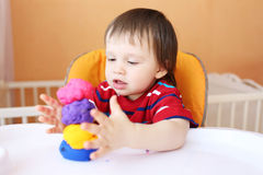 Lovely baby with plasticine at home Stock Photos